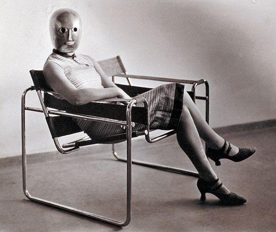(Fotografía de Erich Consemüller - Mujer con una máscara de Oskar Schlemmer, sentada en una silla Wassily, conocida como Modelo B3, diseñada porMarcel Breuer. Bauhaus, 1926)
