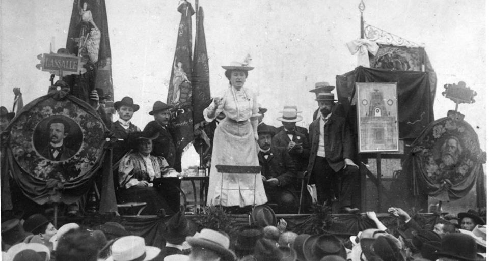 Rosa Luxemburg se dirige a una multitud de Stuttgart en 1907. Aquí está flanqueada por retratos de Karl Marx (derecha) y Ferdinand Lassalle (izquierda), los fundadores del movimiento socialista alemán.